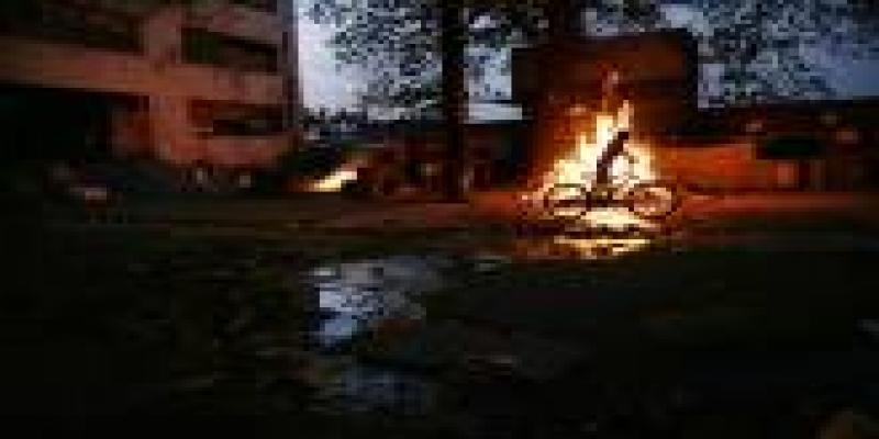Criança anda de bike em frente a casa pegando fogo